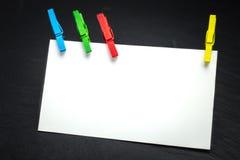 Fermez-vous d'un papier de note et des pinces à linge Photographie stock