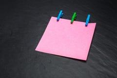 Fermez-vous d'un papier de note rose et des pinces à linge Image stock