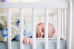 Fermez-vous d'un petit bébé garçon dormant, bébé se situant dans le berceau de bébé Images stock