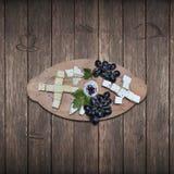 Fermez-vous d'un plateau de pain et de fromage rustiques assortis avec des olives et des raisins photos libres de droits