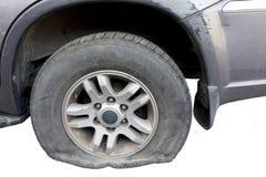 Fermez-vous d'un pneu crevé d'une vieille voiture rouillée portée sur la route de gravier Photographie stock