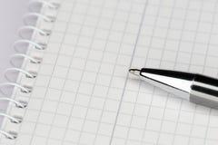 Fermez-vous d'un stylo avec la note Photo stock