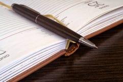 Fermez-vous d'un stylo et d'un carnet photographie stock libre de droits