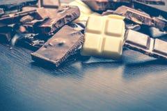 Fermez-vous d'un tas de divers morceaux de chocolat au-dessus de fond en bois foncé Noir, lait, blanc et barres de chocolat d'écr Images libres de droits