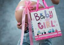 Fermez-vous d'un ventre enceinte mignon de ventre avec le ruban rose Photo libre de droits