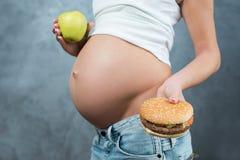 Fermez-vous d'un ventre enceinte mignon de ventre et d'un non sain sain Photo stock