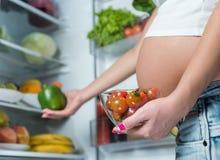 Fermez-vous d'un ventre enceinte mignon de ventre près du réfrigérateur Photos libres de droits