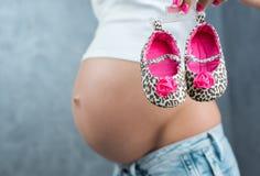 Fermez-vous d'un ventre enceinte mignon et de petites chaussures pour le bébé Photos stock