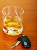 Fermez-vous d'un verre de whiskey avec des clés de voiture sur la table en bois images libres de droits