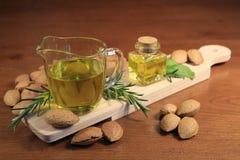 Fermez-vous d'un verre d'huile d'amandes avec quelques épices et amandes sur une planche à découper en bois photographie stock libre de droits