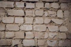 Fermez-vous d'un vieux mur de briques extérieur avec la peinture blanche souillée et de épluchage photo stock