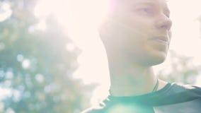 Fermez-vous d'un visage du ` s de jeune homme au soleil clips vidéos