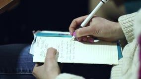 Fermez-vous d'une écriture de main d'auteur de femme dans un carnet banque de vidéos