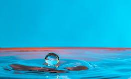 Fermez-vous d'une baisse de l'eau tombant et effectuez sur une eau superficielle photo stock