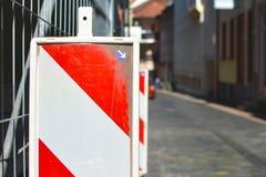 Fermez-vous d'une balise rayée rouge et blanche de sécurité devant la barrière de chantier de construction avec la rue à l'arrièr photo libre de droits