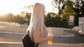 Fermez-vous d'une belle femme aux cheveux longs marchant par la rue Fille décontractée avec le sac noir et tasse de limonade lent clips vidéos