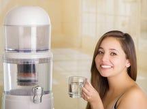 Fermez-vous d'une belle femme de sourire tenant un verre de l'eau, avec un système de filtre d'épurateur de l'eau sur une cuisine images stock