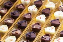Fermez-vous d'une boîte des bonbons au chocolat à lait formés par fantaisie, à blanc et à noir Photographie stock libre de droits