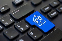 Fermez-vous d'une clé de retour verte avec une icône d'une maison sur l'ordinateur Photo stock