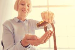 Fermez-vous d'une femme âgée par positif prenant des pilules Photos stock