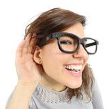 Fermez-vous d'une femme écoutant avec sa main dans l'oreille Images stock