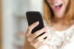 Fermez-vous d'une femme étonnée à l'aide d'un téléphone intelligent à la maison Photo stock