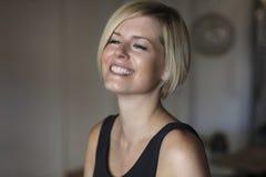 Fermez-vous d'une femme assez blonde souriant et regardant loin Images libres de droits