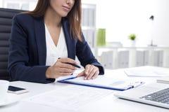 Fermez-vous d'une femme d'affaires bronzée avec un presse-papiers et un stylo Photo libre de droits