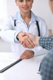 Fermez-vous d'une femme de docteur serrant la main à son patient masculin Concept de médecine et de confiance Images stock
