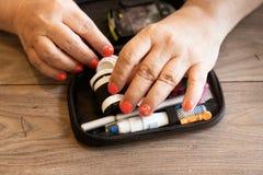 Fermez-vous d'une femme disposant un dispositif de glucometer pour examiner le niveau de glucose photos stock