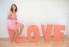 Fermez-vous d'une femme enceinte mignonne avec amour de mot Photo libre de droits