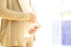 Fermez-vous d'une femme enceinte tenant le ventre Photographie stock libre de droits