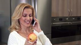 Fermez-vous d'une femme gaie magnifique parlant au téléphone tenant une pomme clips vidéos