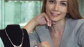 Fermez-vous d'une femme renversante posant avec un collier de diamants au magasin clips vidéos