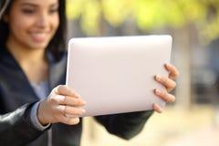 Fermez-vous d'une femme tenant et observant un comprimé numérique Image stock