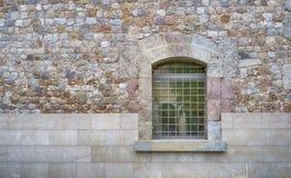Fermez-vous d'une fenêtre avec les barres et le mur image stock