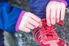 Fermez-vous d'une fille attachant ses chaussures rouges images libres de droits