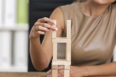 Fermez-vous d'une fille jouant avec les briques en bois Image libre de droits