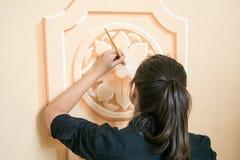 Fermez-vous d'une fille (les cheveux foncés et les vêtements noirs) décorant un mur avec un élément moteur floral avec une brosse Photo libre de droits