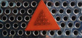 Fermez-vous d'une grille brillante en m?tal avec une triangle de avertissement se refl?tante de lumi?re orange image stock