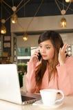 Fermez-vous d'une jeune femme d'affaires soumise à une contrainte dans le bureau tandis qu'elle utilise un téléphone portable Con photo stock