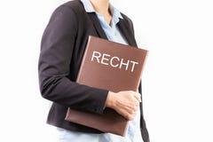 Fermez-vous d'une jeune femme dans un costume tenant un dossier avec un texte allemand : LOI image libre de droits