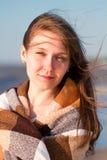 Fermez-vous d'une jeune femme de sourire couverte de couverture à l'être photos stock