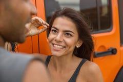 Fermez-vous d'une jeune femme de sourire parlant à un type Image stock
