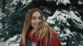 Fermez-vous d'une jeune jolie fille dans des vêtements chauds se tenant près des arbres de Noël avec de longs cheveux secouant sa banque de vidéos