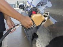 Fermez-vous d'une main tenant le gicleur d'essence Photo libre de droits