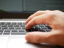 Fermez-vous d'une main d'un homme travaillant au-dessus d'un ordinateur portable et à l'aide de la protection de voie image stock