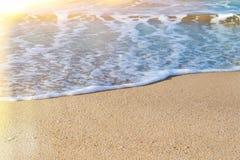 Fermez-vous d'une mousse de mer blanche sur un sable côtier jaune un jour ensoleillé Fond marin avec l'éruption chromosphérique photo stock