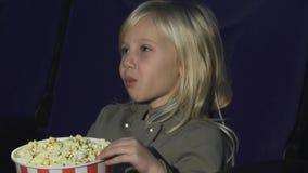 Fermez-vous d'une petite fille adorable mangeant du maïs éclaté tandis qu'au théâtre de film banque de vidéos
