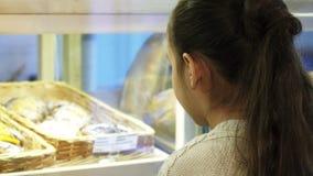 Fermez-vous d'une petite fille mignonne souriant à l'appareil-photo à la boulangerie banque de vidéos